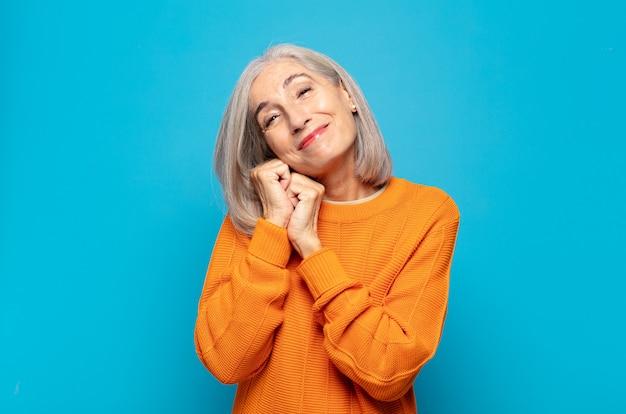 Zakochana kobieta w średnim wieku, wyglądająca słodko, uroczo i szczęśliwie, romantycznie uśmiechnięta z rękami obok twarzy