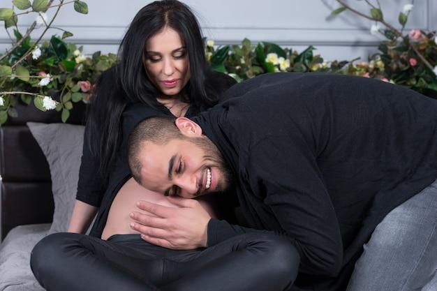 Zakochana międzynarodowa para, mężczyzna słucha brzucha ciężarnej żony, siedząc na szarym, wygodnym łóżku w sypialni