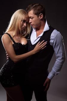 Zakochana młoda para, młoda kobieta w seksownej czarnej sukience i zakochany mężczyzna przytulający ją