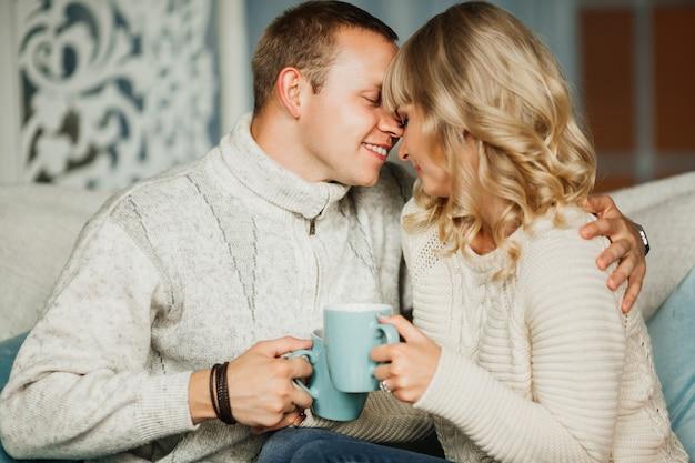 Zakochana młoda para na kanapie, śmiejąc się i pijąc kawę, herbatę
