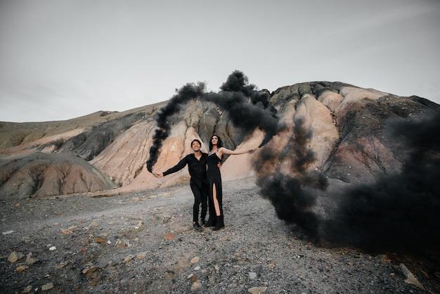 Zakochana para azjatycka zapaliła w górach czarne bomby dymne. kolorowy dym