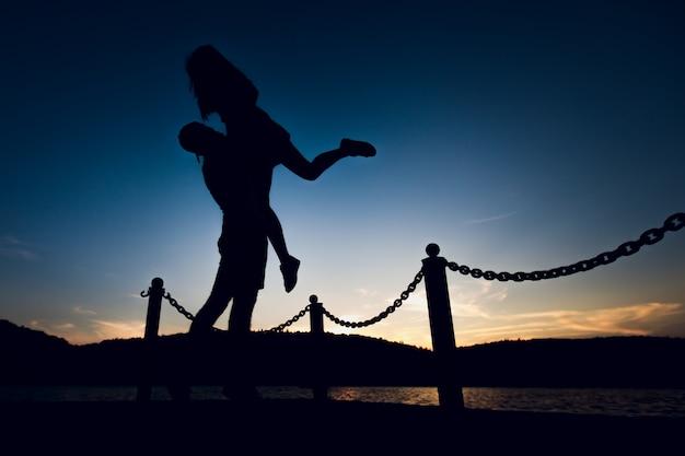 Zakochana para bawi się na nabrzeżu plaży lub rzeki: mężczyzna niosący dziewczynę w ramionach i na ramieniu