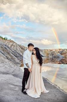 Zakochana para całuje i przytula się na tle tęczy i gór. mężczyzna i kobieta się kochają. wspaniała sceneria