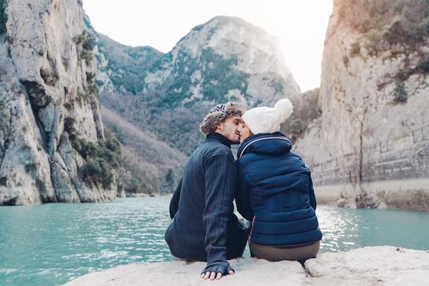 Zakochana para całuje się przed górskim krajobrazem w zimie. pojęcie o miłości, podróżach, ludziach i stylu życia