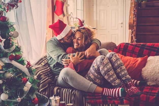 Zakochana para cieszy się i świętuje wigilijny poranek w domu, przytulając się i całując, usiądź na kolorowej i udekorowanej sofie w domu