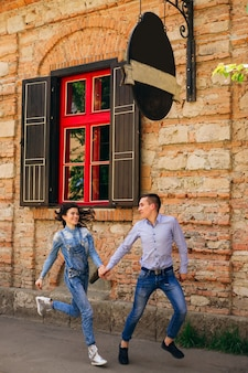 Zakochana para dobrze się bawi. trzymają się za ręce i biegną po chodniku w pobliżu ceglanego budynku z oknami