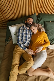 Zakochana para dorosłych czeka na dziecko. mężczyzna i jego ciężarna żona wygrzewają się w łóżku w sypialni