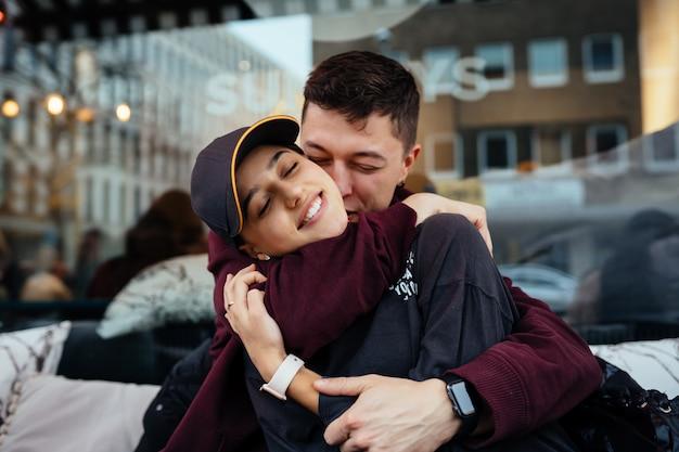 Zakochana para. facet i dziewczyna przytulają się przy stoliku w kawiarni na świeżym powietrzu.