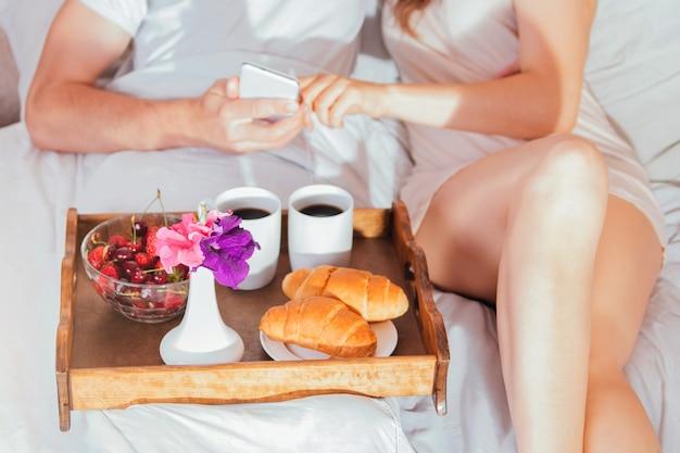 Zakochana para je śniadanie w łóżku za pomocą telefonu?