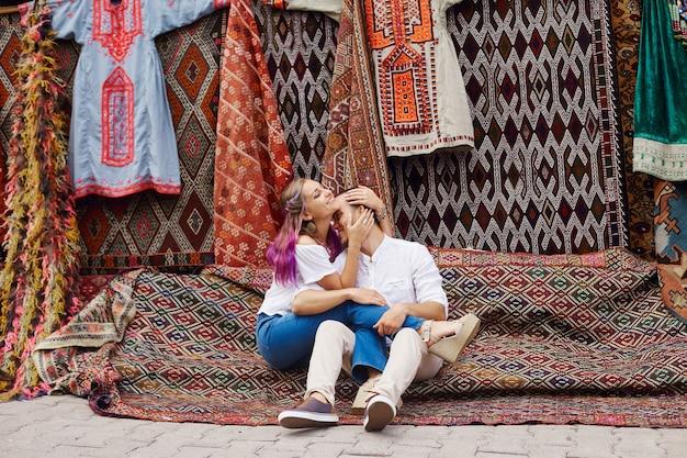 Zakochana para kupuje dywan i ręcznie robione tekstylia na orientalnym targu w turcji. uściski i wesołe, szczęśliwe twarze mężczyzn i kobiet