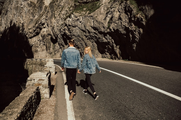 Zakochana para, mężczyzna i dziewczyna idą drogą w dal, trzymając się za ręce.