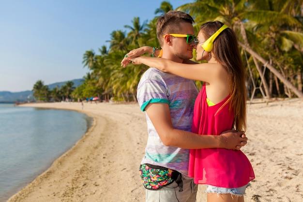 Zakochana para młodych hipster, tropikalna plaża, wakacje, modny styl lato, okulary przeciwsłoneczne, słuchawki