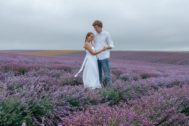 Zakochana para na lawendowym polu w białych ubraniach