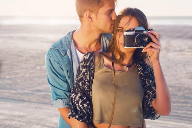 Zakochana para pozuje na wieczornej plaży, młoda hipster dziewczyna i jej przystojny chłopak robi zdjęcia aparatem retro. ciepłe światło słońca.