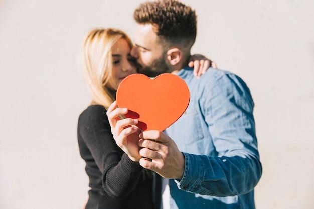 Zakochana para pozuje z czerwonym sercem