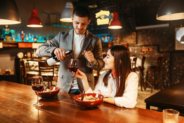 Zakochana para przy drewnianym barze, romantyczne świętowanie randki, kolacja z pastą i czerwonym winem. miłośnicy spędzają czas w pubie, mąż i żona relaksują się razem w nocnym klubie