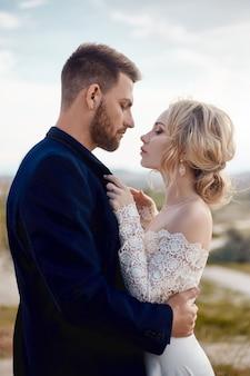 Zakochana para przytula się i całuje w bajecznych górach w przyrodzie. dziewczyna w długiej białej sukni z bukietem kwiatów w jej ręce, mężczyzna w kurtce. ślub w naturze, związki i miłość