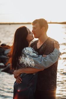Zakochana para przytula się nad brzegiem morza w słońcu.