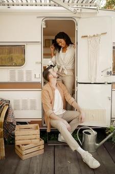 Zakochana para przytula się w przyczepie kempingowej. mężczyzna i kobieta podróżują vanem, wakacje w kamperze, obozowicze wypoczywają w samochodzie kempingowym