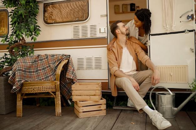 Zakochana para przytula się w rv, biwakuje w przyczepie. mężczyzna i kobieta podróżują vanem, romantyczne wakacje w kamperze, obozowicze w samochodzie kempingowym