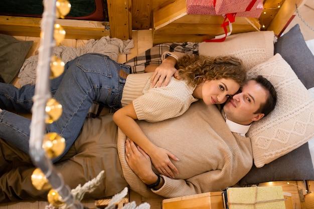 Zakochana para przytulająca się, ciesząca się wolnym czasem i bawiąca się w przyczepie w pobliżu świątecznych prezentów