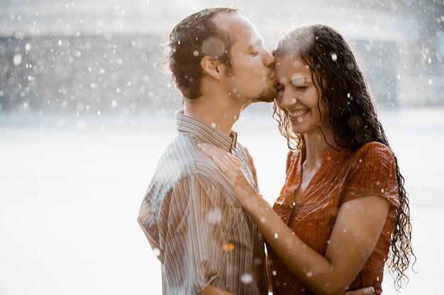 Zakochana para przytulanie i całowanie pod deszczem. są mokre i uśmiechnięte