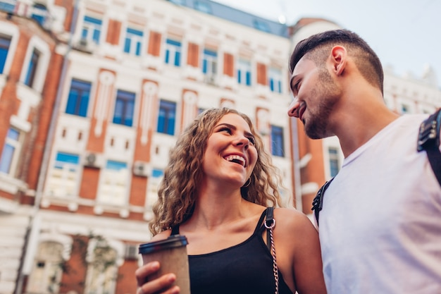 Zakochana para rasy mieszanej spaceru w mieście. arabski mężczyzna i biała kobieta piją kawę, rozmawiają i śmieją się na zewnątrz