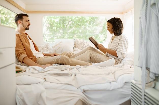 Zakochana para relaksuje się w sypialni, biwakuje w przyczepie. mężczyzna i kobieta podróżują vanem, wakacje w kamperze, obozowicze odpoczywają w samochodzie kempingowym