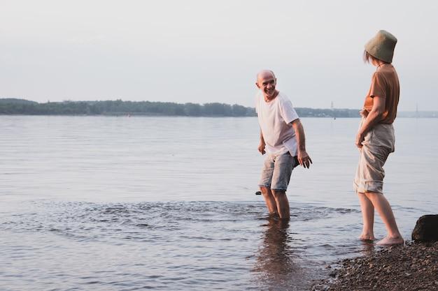 Zakochana para seniorów spacerująca i mająca wentylator na plaży w okresie letnim