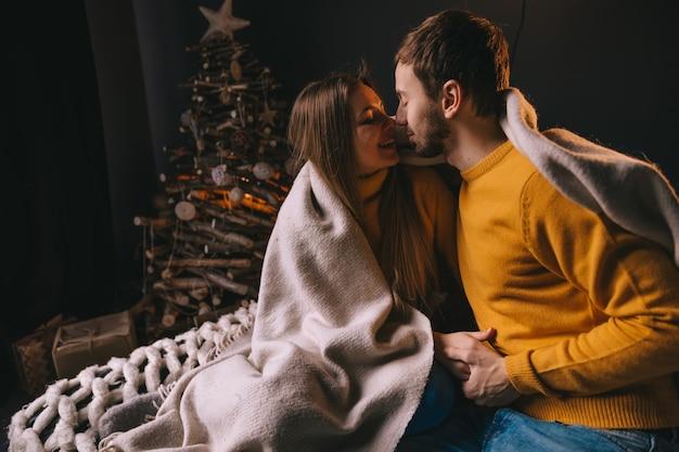 Zakochana para siada na łóżku i chce się pocałować. girlandy na ścianie i drzewo przy łóżku.