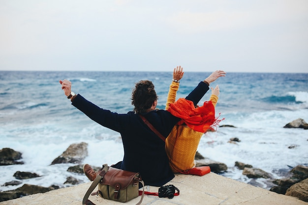 Zakochana para siedzi na nabrzeżu i patrzy na morze