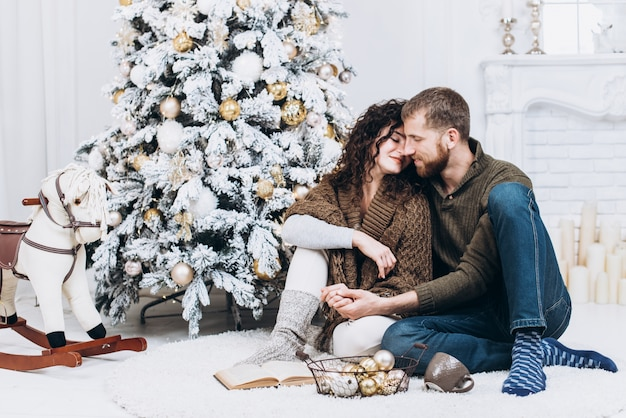 Zakochana para siedzi na podłodze salonu wymiany świątecznych prezentów