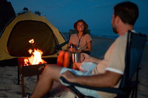Zakochana para siedzi obok namiotu na składanych krzesłach przy ognisku, pijąc wieczorem herbatę nad brzegiem morza.