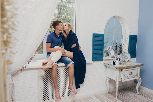 Zakochana para siedzi w domu w oknie. czuły, kochający uścisk nowożeńców. zabawny poranek szczęśliwy nastrój kochającej się pary. dziewczyna przytula się do romantycznych uczuć chłopaka. walentynki