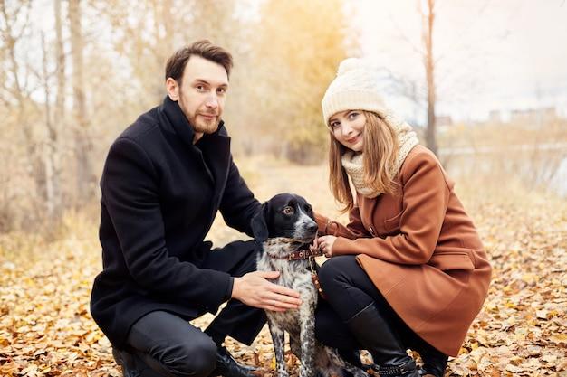 Zakochana para spacerująca z psem w parku
