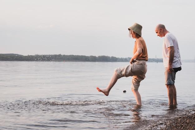 Zakochana para starszych spacerująca po brzegu morza lub rzeki i wspólna zabawa
