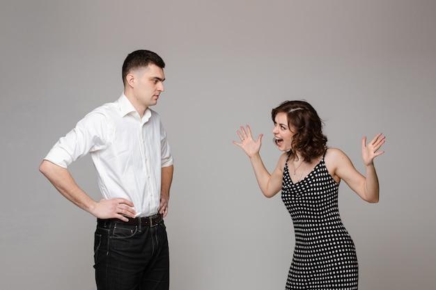Zakochana para stoi i krzyczy do siebie, obraz na szarym tle
