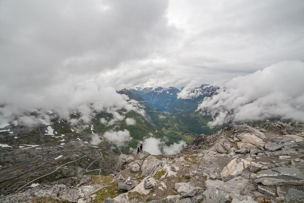 Zakochana para stoi na skraju góry widok na fiord geiranger i drogę orłów w pochmurną pogodę z góry dalsnibba