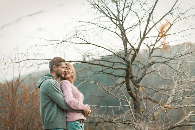 Zakochana para stoi przeciwko naturze i czule tuli się