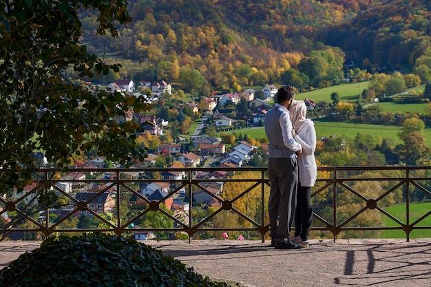 Zakochana para stoi przy płocie i podziwia piękny widok na dolinę