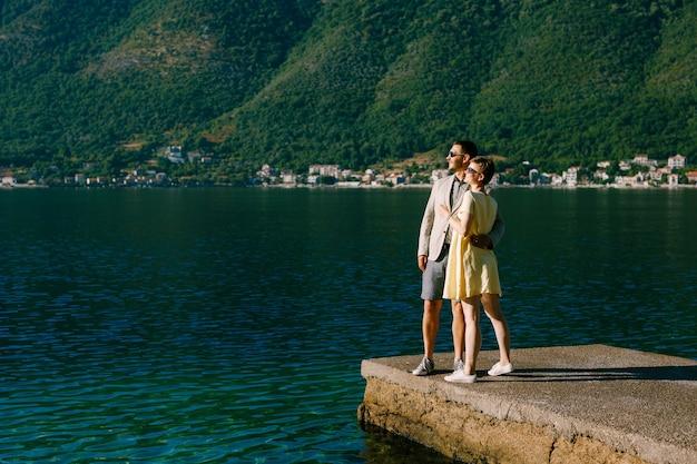 Zakochana para stoi przytulona na molo w zatoce kotor w pobliżu perast