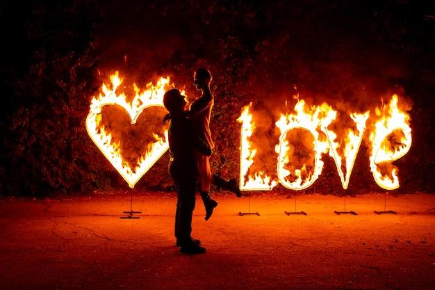 Zakochana para tańczy w pobliżu płonącego ognia, litery miłości i serca