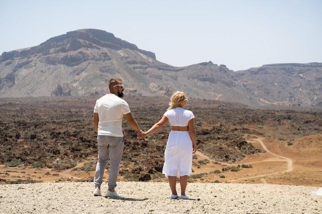 Zakochana para trzyma się za ręce w kraterze wulkanu teide. teneryfa, wyspy kanaryjskie.