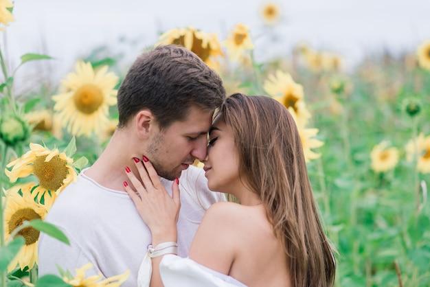 Zakochana para w białych sukienkach całuje się, uśmiecha się, hulając w polu słoneczników