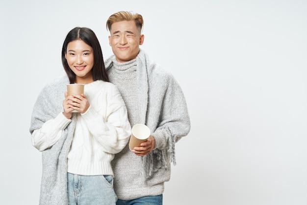 Zakochana para w ciepłych ubraniach przytula się do siebie z filiżanką kawy w ręku