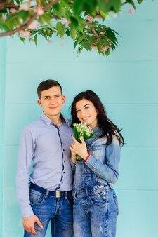 Zakochana para w dżinsowych ubraniach. kobieta trzyma bukiet kwiatów