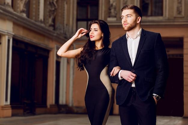 Zakochana para w eleganckim stroju spaceru ulicą starego miasta. ładna brunetka kobieta z czerwonymi ustami i jej przystojny chłopak mają czas wolny.