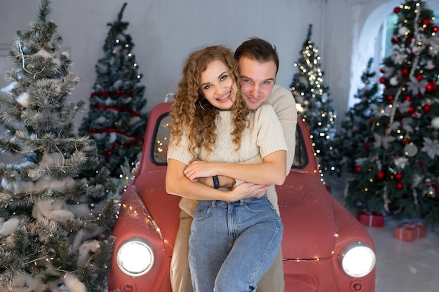 Zakochana para w pobliżu ładnie udekorowanej choinki i czerwonego samochodu