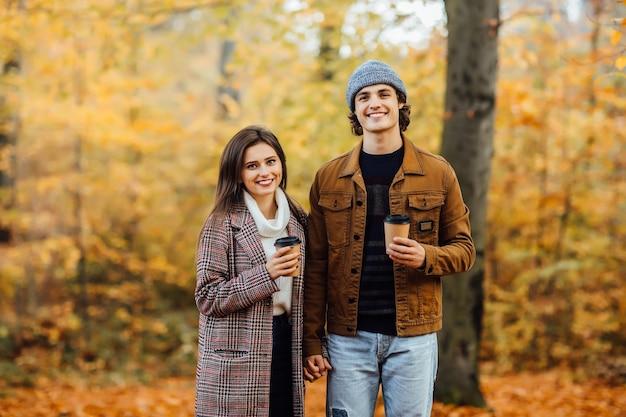 Zakochana para w szalikach siedzi w parku, trzymając filiżanki herbaty lub kawy