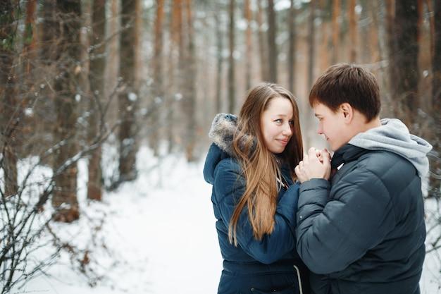 Zakochana para zabawy w ferie zimowe. śnieg zimowy las na tle.